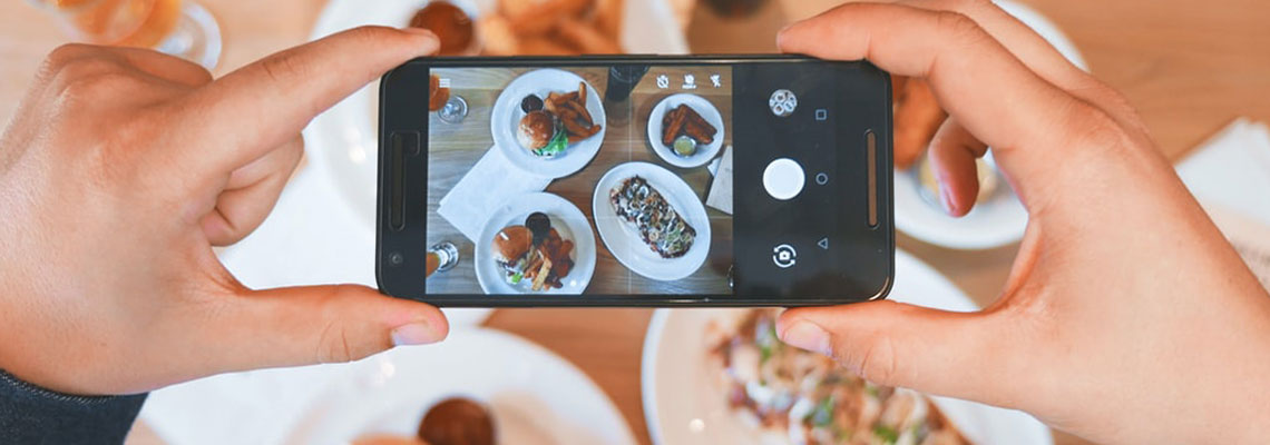Photo d'un influenceur food qui prend son plat en photo avec son téléphone